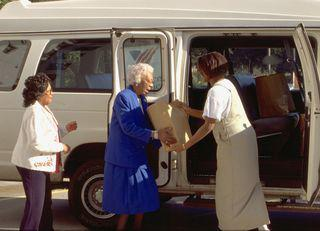 women loading boxes into a van