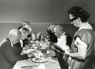 founder maud booth praying with people over food