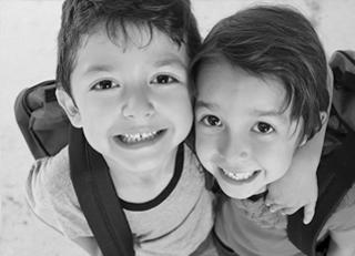 boy and girl wearing backpacks and smiling