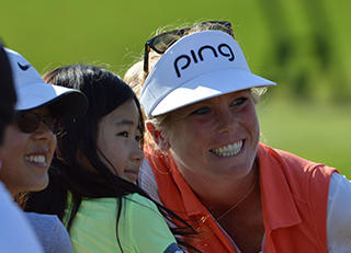 LPGA golfer taking a photo with children in the crowd