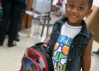 Boy with school supplies from Operation Backpack
