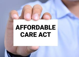 "Person holding notecard that reads ""Affordable Care Act"""