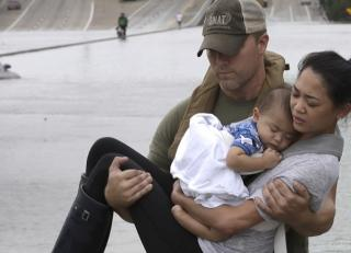 Police Officer Carrying Mother and Child During Hurricane Harvey