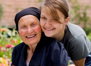 elderly woman with younger woman at an outside dining table