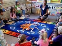 Nursery school kids with their teacher sitting on the floor around a blaket