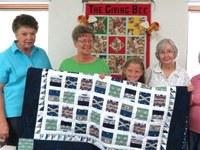 Women and a little girl smiling and holding up a quilt they made