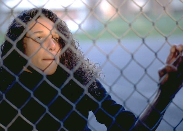 A young woman looking out the fence of a prison