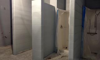 It's happening!  Walls are painted, the ceiling is in, and the showers are installed.  Here's a sneak peek of the new showers in the men's room!