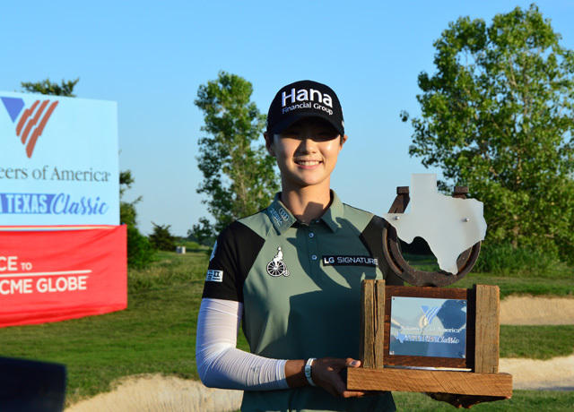 Winning LPGA golfer accepting trophy at sponsor event
