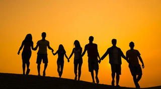 A group of people hold hands in silhouette.
