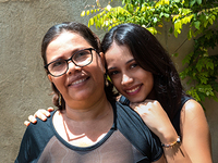 Mother-standing-with-teenage-daughter-leaning-on-her-shoulder-outside-smiling-at-camera